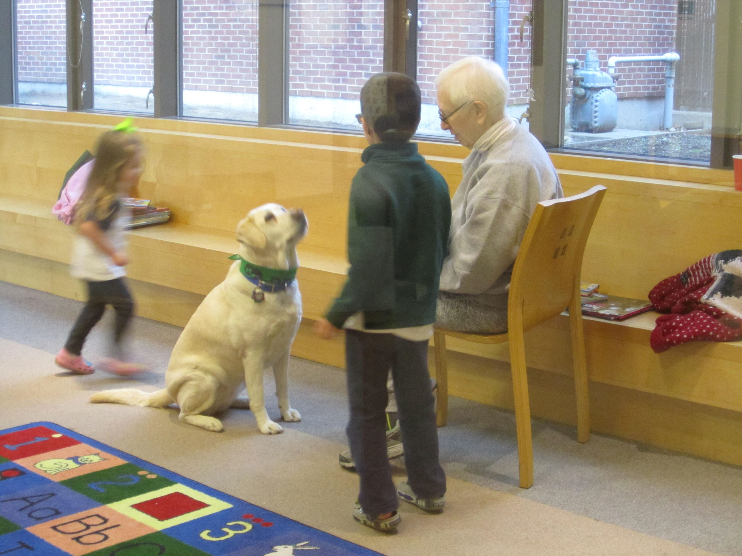 Two children standing next to a golden Labrador sitting on the floor looking up at one of the childr