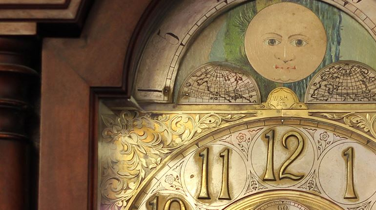 Image shows the detail of an antique clock face.