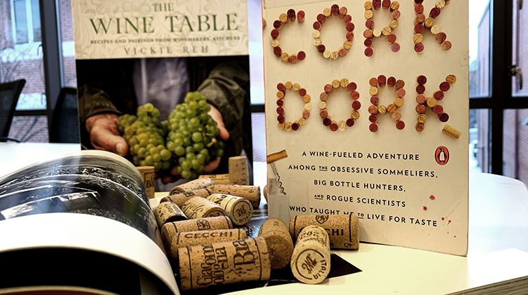 Photo of two books standing upright behind a pile of wine corks.